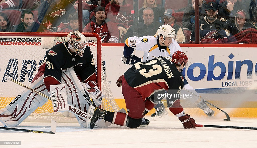Roman Josi #59 of the Nashville Predators tries to work the puck around Oliver Ekman-Larsson #23 of the Phoenix Coyotes and goalie Chad Johnson #31 at Jobing.com Arena on January 28, 2013 in Glendale, Arizona.