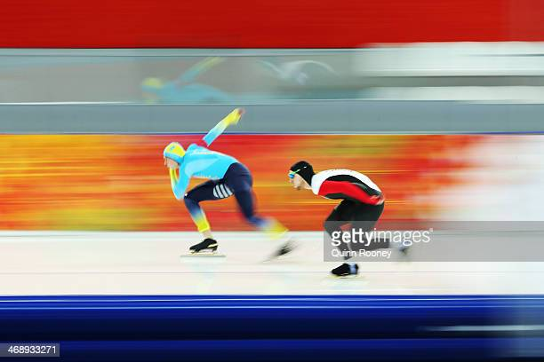 Roman Krech of Kazakhstan and William Dutton of Canada competes during the Men's 1000m Speed Skating event during day 5 of the Sochi 2014 Winter...