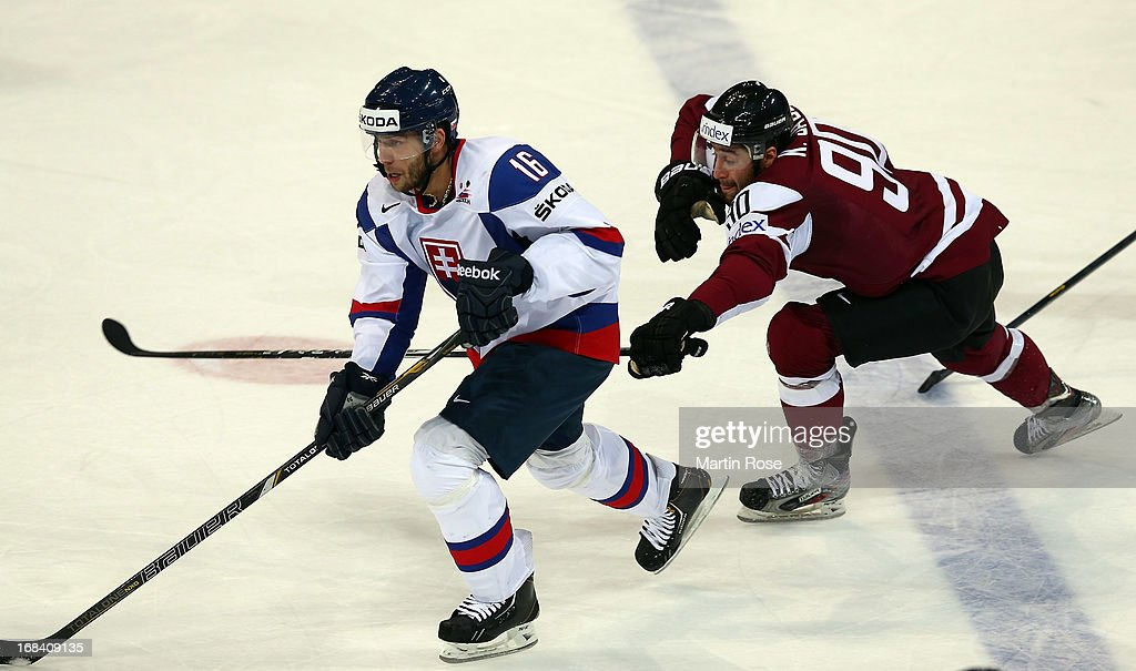 Roman Kukumberg (L) of Slovakia and Koba Jass (R) of Latvia battle for the puck during the IIHF World Championship group H match between Russia and France at Hartwall Areena on May 9, 2013 in Helsinki, Finland.