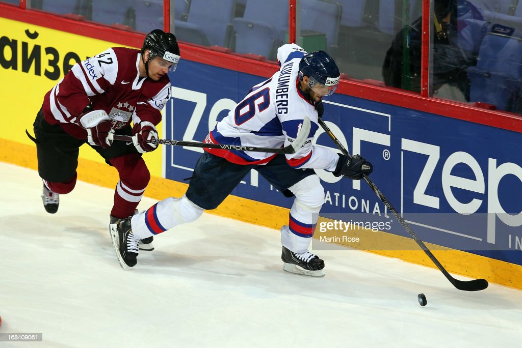 Roman Kukumberg (R) of Slovakia and Vitalijs Pavlovs (L) of Latvia battle for the puck during the IIHF World Championship group H match between Russia and France at Hartwall Areena on May 9, 2013 in Helsinki, Finland.