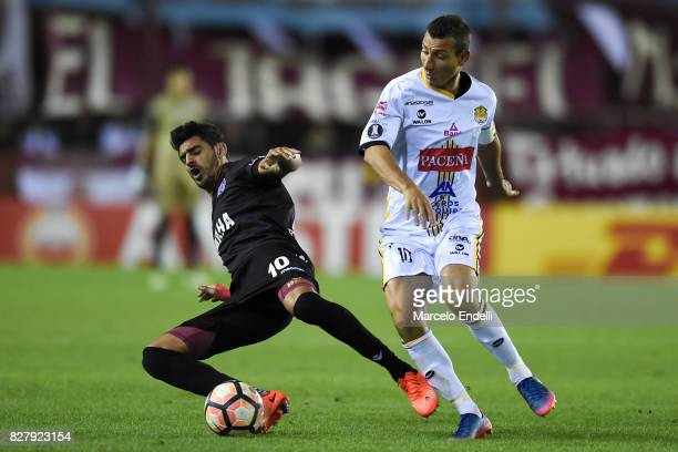 Roman Martinez of Lanus fights for ball with Pablo Escobar of The Strongest during the second leg match between Lanus and The Strongest as part of...