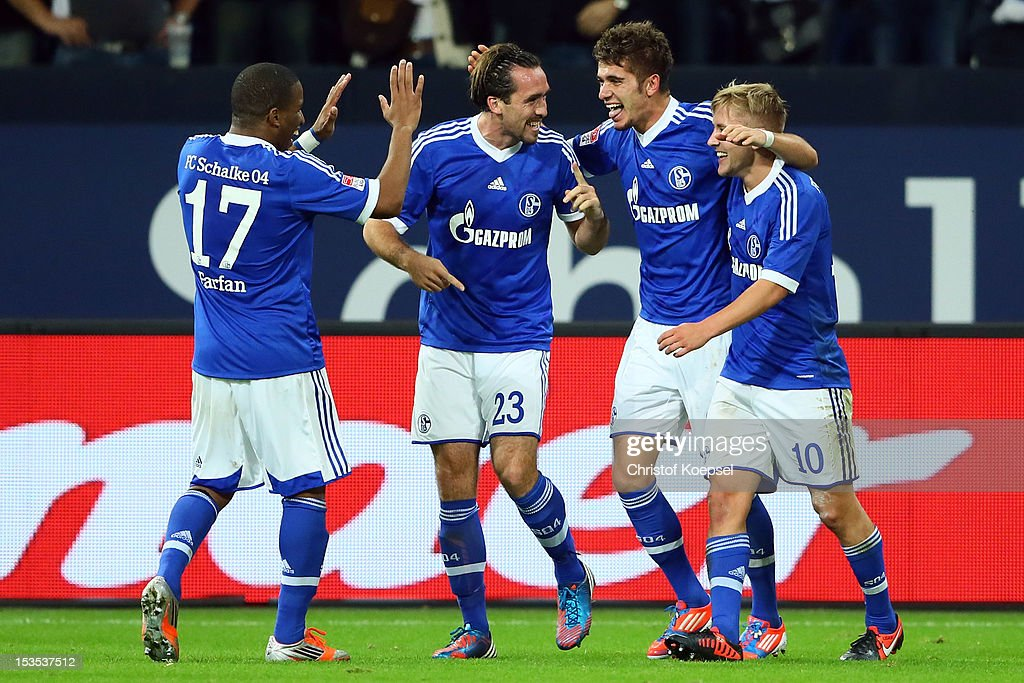 Roman Neustaedter of Schalke (2nd R) celebrates the third goal with Jefferson Farfan (L), Christian Fuchs (2nd L) and Lewis Holtby (R) during the Bundesliga match between FC Schalke 04 and VfL Wolfsburg at Veltins-Arena on October 6, 2012 in Gelsenkirchen, Germany.