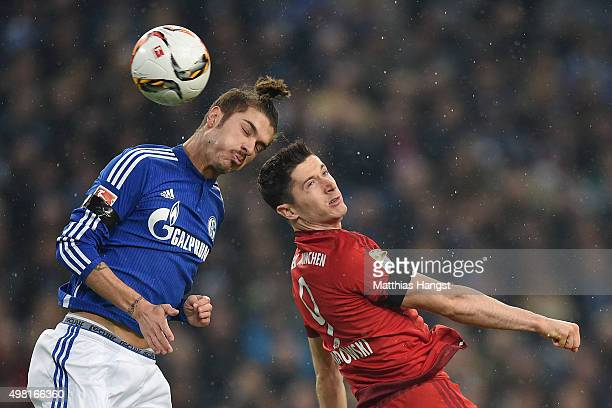Roman Neustaedter of Schalke jumps for a header with Robert Lewandowski of Muenchen during the Bundesliga match between FC Schalke 04 and FC Bayern...