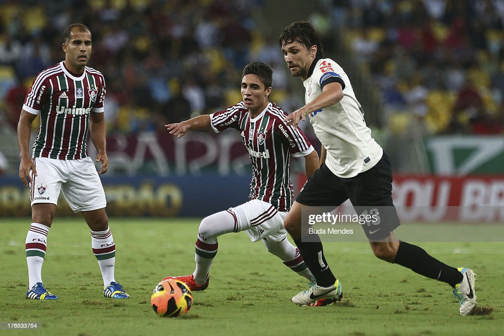 Roman (C) of Fluminense struggles for the ball with Paulo Andre (R) of Corinthians during a match between Fluminense and Corinthians as part of Brazilian Championship 2013 at Maracana Stadium on August 14, 2013 in Rio de Janeiro, Brazil.