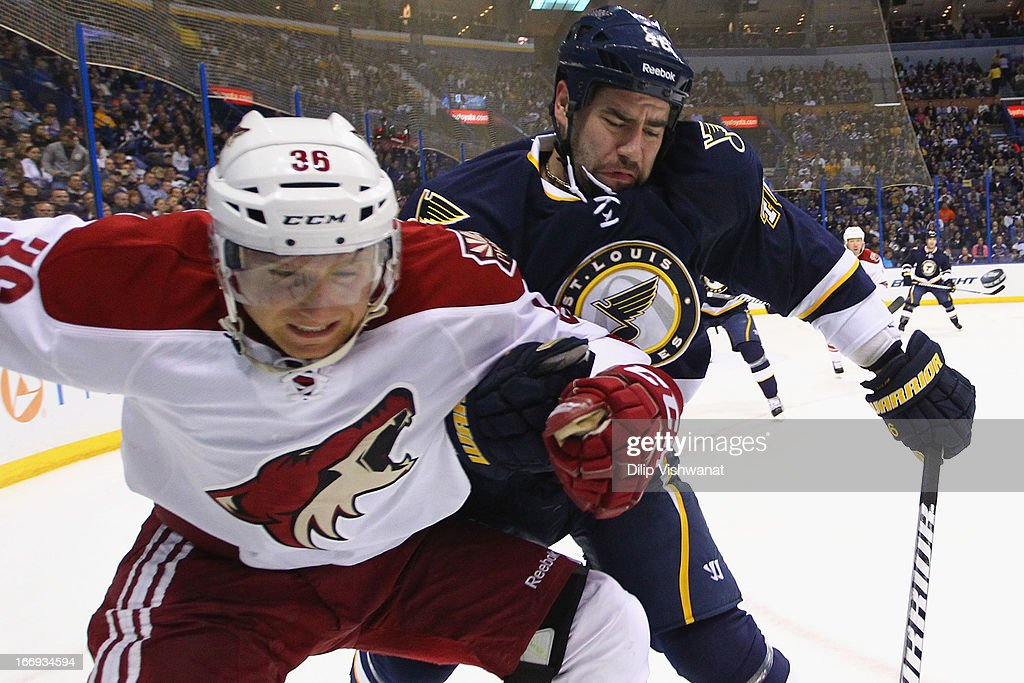 Roman Polak #46 of the St. Louis Blues and Rob Klinkhammer #36 of the Phoenix Coyotes fight for a loose puck in the first period at the Scottrade Center on April 18, 2013 in St. Louis, Missouri. The Blues beat the Coyotes 2-1 in a shootout.