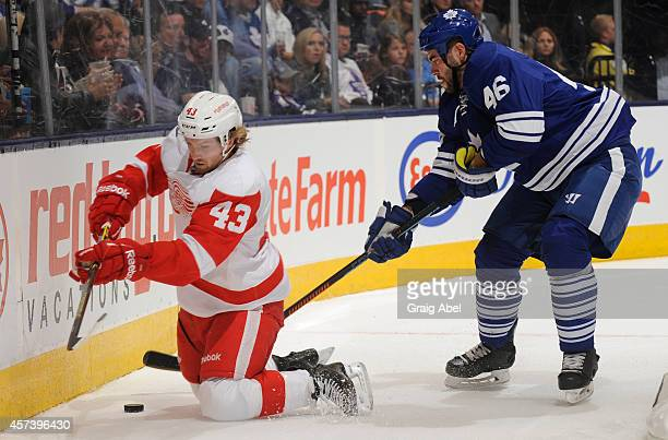 Roman Polak of the Toronto Maple Leafs battles for the puck with Darren Helm of the Detroit Red Wings during NHL game action October 17 2014 at the...