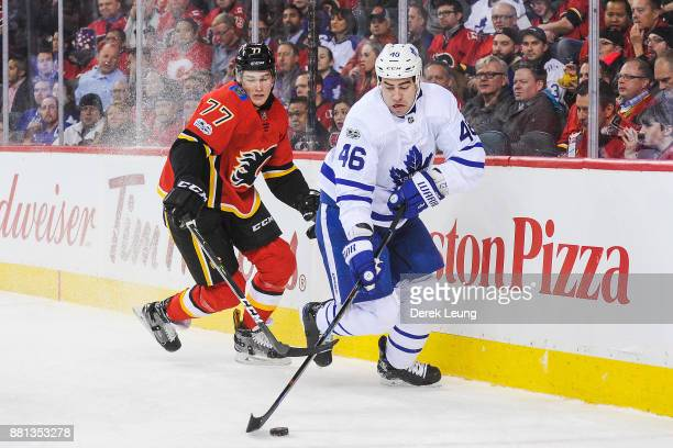 Roman Polak of the Toronto Maple Leafs carries the puck against Mark Jankowski of the Calgary Flames during an NHL game at Scotiabank Saddledome on...