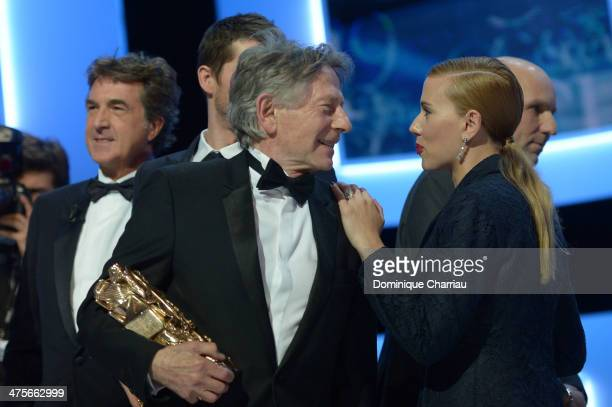 Roman Polanski holds the Best Director award for 'Venus in Fur' while actress Scarlett Johansson holds the Honorary Cesar award on stage during the...