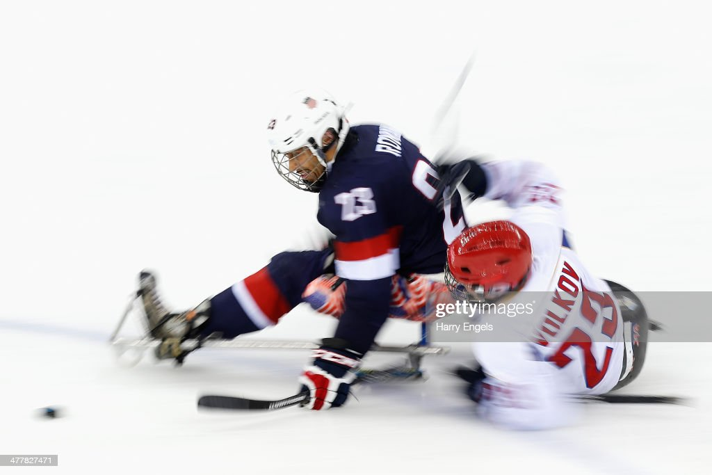Roman Rico of USA is tackled by Ilia Volkov of Russia during the Ice Sledge Hockey Preliminary Round Group B match between USA and Russia at the Shayba Arena during day four of the Sochi 2014 Paralympic Winter Games on March 11, 2014 in Sochi, Russia.