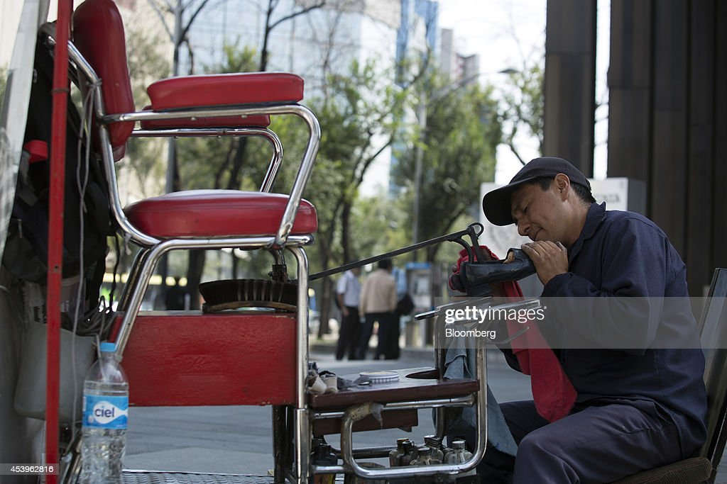 Roman Sanchez, 34, works at a shoe shine stand on Reforma Avenue in Mexico City, Mexico, on Thursday, Aug. 21, 2014. Mexican consumer prices rose more than analysts expected in the first half of August and the unemployment rate rose to 5.47 percent in July compared with 4.8 percent in June. Photographer: Susana Gonzalez/Bloomberg via Getty Images