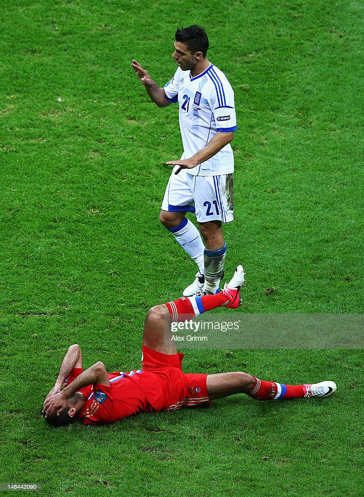 <a gi-track='captionPersonalityLinkClicked' href=/galleries/search?phrase=Roman+Shirokov&family=editorial&specificpeople=2348160 ng-click='$event.stopPropagation()'>Roman Shirokov</a> of Russia lies on the pitch injured as Kostas Katsouranis of Greece reacts during the UEFA EURO 2012 group A match between Greece and Russia at The National Stadium on June 16, 2012 in Warsaw, Poland.