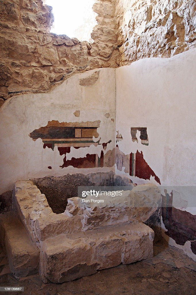 Roman style Bath House built by Herod. Dressing Room (apodyterium) showing fresco on wall and immersion tub put in by Jewish zealots who occupied the fort before their fight against the Romans. Shore of the Dead Sea at Ein Gedi & Massada, Israel. : Stock Photo