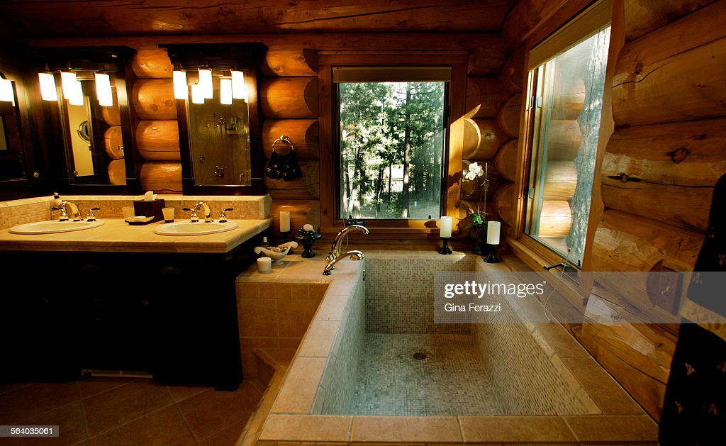 a roman style tub along with bathroom mirror frames cut to fit around thick logs make