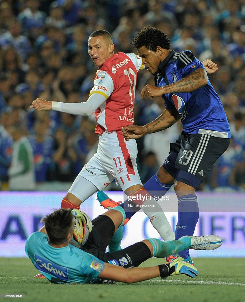 Roman Torres (R) and goalkeeper Nicolas Vikonis (L) of Millonarios struggles for the ball with <a gi-track='captionPersonalityLinkClicked' href=/galleries/search?phrase=Luis+Paez&family=editorial&specificpeople=5348332 ng-click='$event.stopPropagation()'>Luis Paez</a> (C) of Santa Fe during a match between Millonarios and Santa Fe as part of 10th round of Liga Aguila I 2015 at Nemesio Camacho El Campin Stadium on March 14, 2015 in Bogota, Colombia.