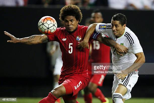Roman Torres of Panama battles for the ball with Carlos Esquivel of Mexico in the run up to the referee awarding a last minute penalty to Mexico in...