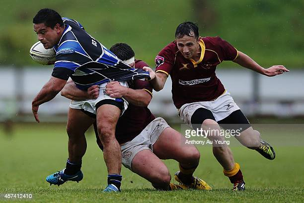 Roman Tutahua of Wanganui makes a run against Carl Carmichael and Paul Olsen of King Country during the Lochore Cup Semi Final match between King...