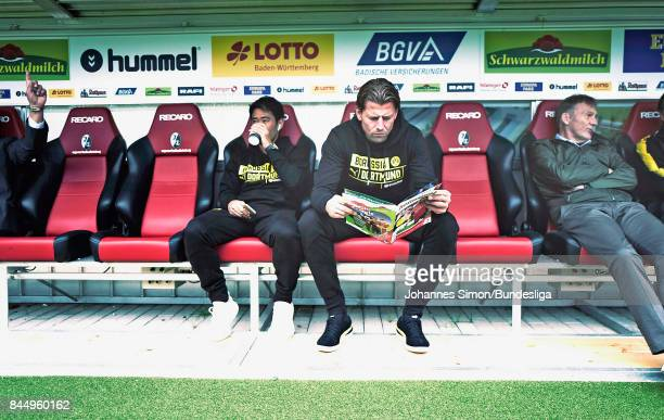 Roman Weidenfeller goalkeeper of Dortmund and team mate Shinji Kagawa sit on the bench prior to the Bundesliga match between SportClub Freiburg and...