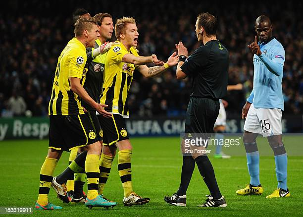 Roman Weidenfeller of Borussia Dortmund and his team mates protest to Referee Pavel Kralovec after he awarded a penalty kick to City during the UEFA...
