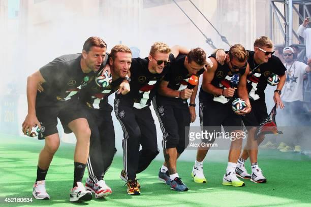 Roman Weidenfeller Shkodran Mustafi Andre Schuerrle Miroslav Klose Mario Goetze and Toni Kroos celebrate on stage at the German team victory ceremony...