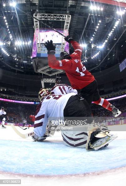 Roman Wick of Switzerland falls to the ice after tripping over Edgars Masalskis of Latvia during the Men's Ice Hockey Qualification Playoff game on...