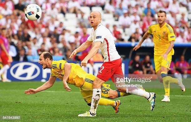 Roman Zozulya of Ukraine goes down under pressure from Michal Pazdan of Poland during the UEFA EURO 2016 Group C match between Ukraine and Poland at...