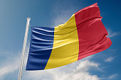 Romania flag is waving at a beautiful and peaceful sky in day time while sun is shining. 3D Rendering