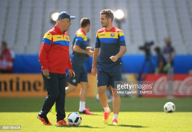Romania manager Anghel Iordanescu speaks with Alexandru Chipciu during a training session at the Stade de France Paris before their game Euro 2016...