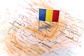 The flag of Romania pinned on the map. Horizontal orientation. Macro photography.