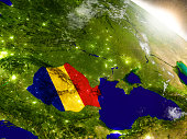 Romania with embedded flag on planet surface during sunrise. 3D illustration with highly detailed realistic planet surface and visible city lights. 3D model of planet created and rendered in Cheetah3D