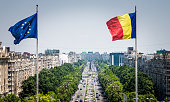 Close up image of the Romanian flag and the European Union (EU) flags flying at the top of the Palace of Parliament in Bucharest, Romania. In the distance we can see the main street of Bucharest stret