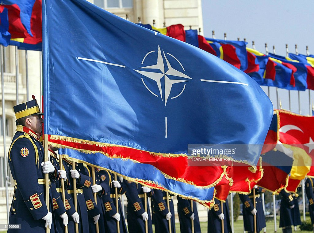 Romanian army soldiers from the guard regiment holds NATO membership countries flags during the ceremony of NATO flag raising in Bucharest 02 April...