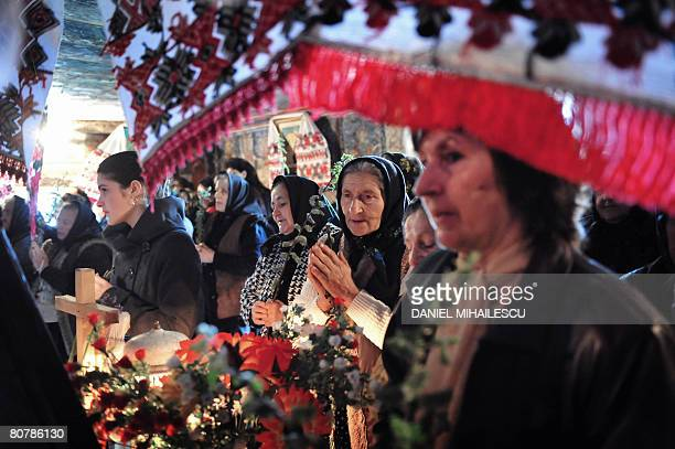 Romanian believers prays during the Palm Sunday religious service outside the Greco Catholic wooden church from Sisesti village 620km north from...
