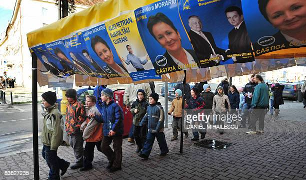 Romanian children walk under election posters of the National Liberal Party in the town of ClujNapoca 480 kms northwest of Bucharest on November 26...