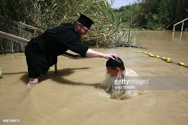 A Romanian Christian Orthodox priest baptizes a pilgrim in the water of the Jordan River as part of their Easter pilgrimage to the Holy Land on April...