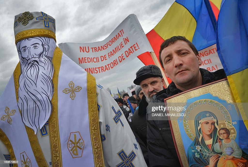 Romanian christian-orthodox believers carry Romanian flags, replicas of the religious icons and a banner that reads 'Don't turn family doctors into managers of data' as they stage a protest against the issue of electronic chip ID's in front of the Romanian Parliament headquarters in Bucharest, Romania on March 14, 2013. Around 400 people mobilized by Orthodox organizations gathered in a protest claiming that the use of chip ID's will narrow the liberty of movement and the liberty of individuals. AFP PHOTO / DANIEL MIHAILESCU