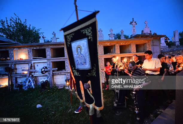 Romanian christianorthodox believers walk around a church holding lit candles during the religious service commemorating the death of Jesus by...