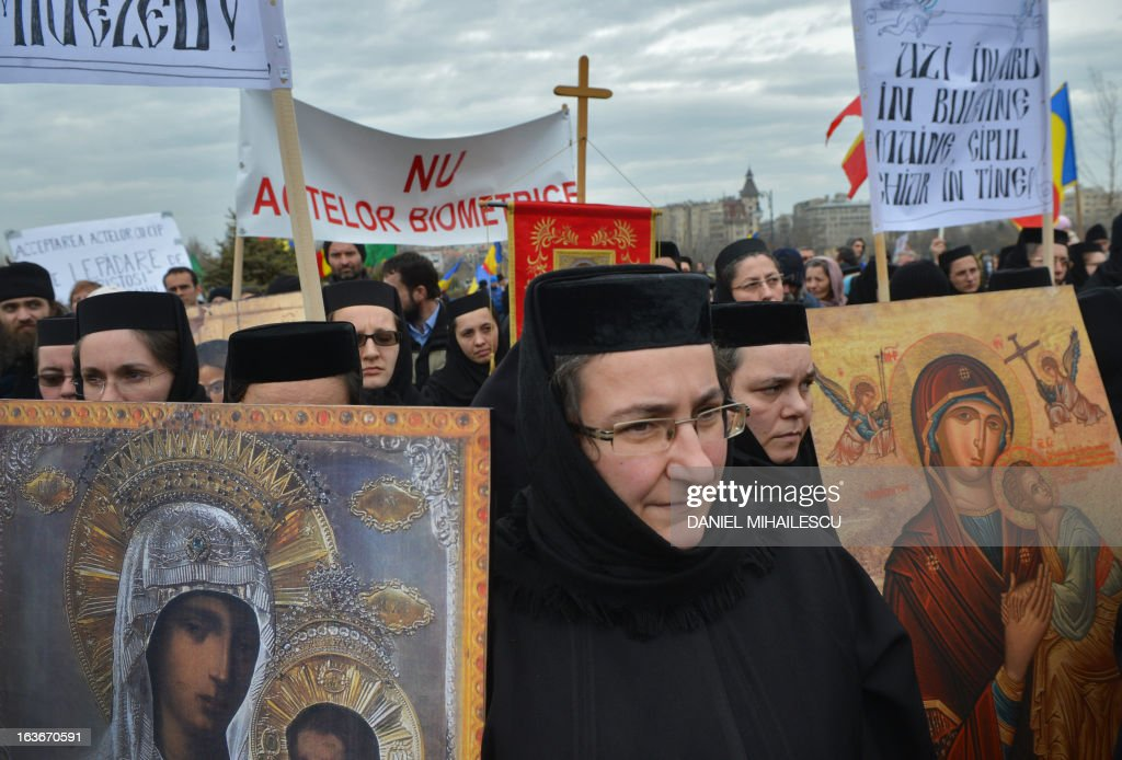 Romanian christian-orthodox nuns and believers carry the replica of religious icons and the crucifix to stage a protest against the issue of electronic chip ID's in front of the Romanian Parliament headquarters in Bucharest, Romania on March 14, 2013. Around 400 people mobilized by Orthodox organizations gathered in a protest claiming that the use of chip ID's will narrow the liberty of movement and the liberty of individuals. AFP PHOTO / DANIEL MIHAILESCU