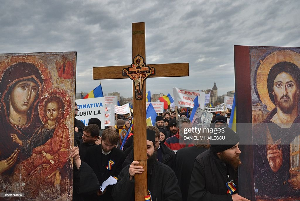 Romanian christian-orthodox priests and believers carry the replica of religious icons and the crucifix to stage a protest against the issue of electronic chip ID's in front of the Romanian Parliament headquarters in Bucharest, Romania on March 14, 2013. Around 400 people mobilized by Orthodox organizations gathered in a protest claiming that the use of chip ID's will narrow the liberty of movement and the liberty of individuals.