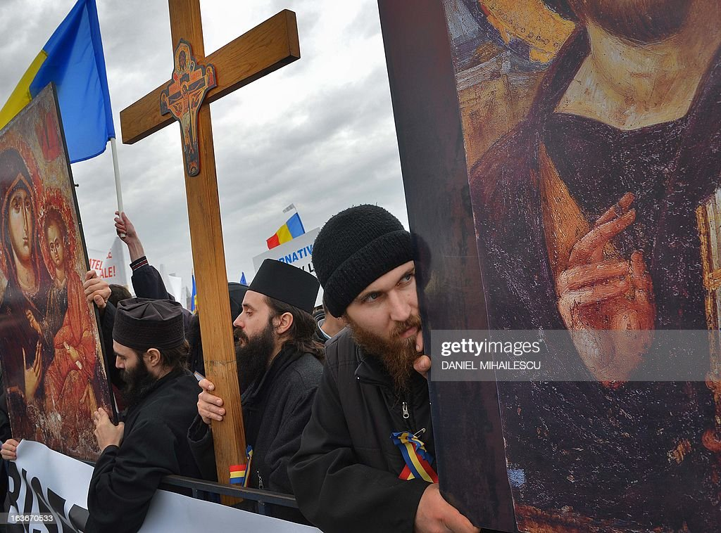 Romanian christian-orthodox priests and believers carry the replica of religious icons and the crucifix to stage a protest against the issue of electronic chip ID's in front of the Romanian Parliament headquarters in Bucharest, Romania on March 14, 2013. Around 400 people mobilized by Orthodox organizations gathered in a protest claiming that the use of chip ID's will narrow the liberty of movement and the liberty of individuals. AFP PHOTO / DANIEL MIHAILESCU