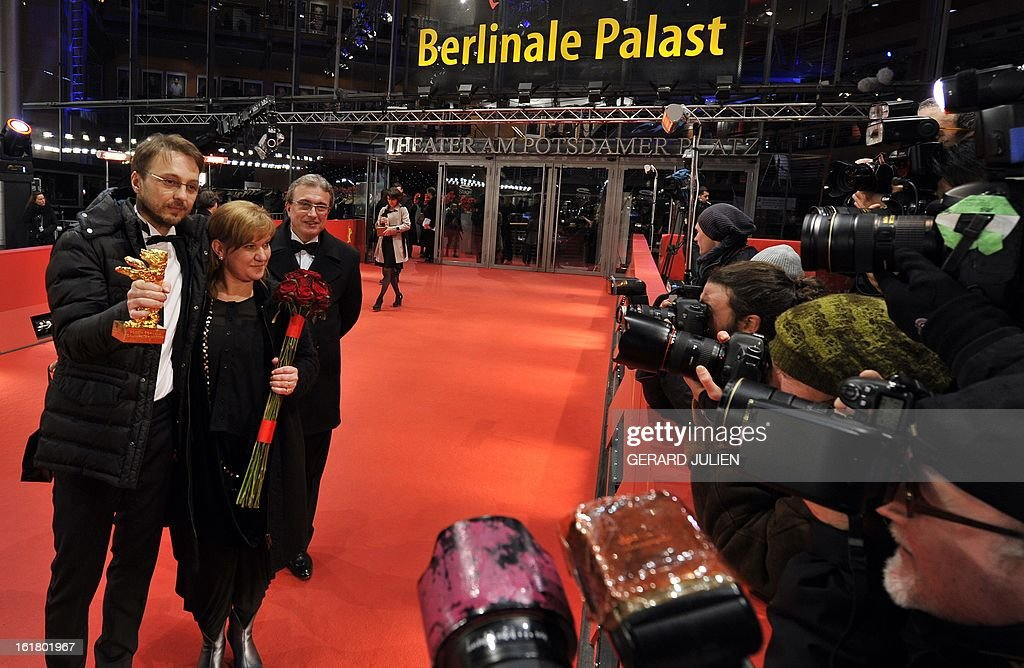 Romanian director Calin Peter Netzer holds his Golden Bear he for the Best Film for his movie Pozitia Copilului as he poses with producer Ada Solomon...
