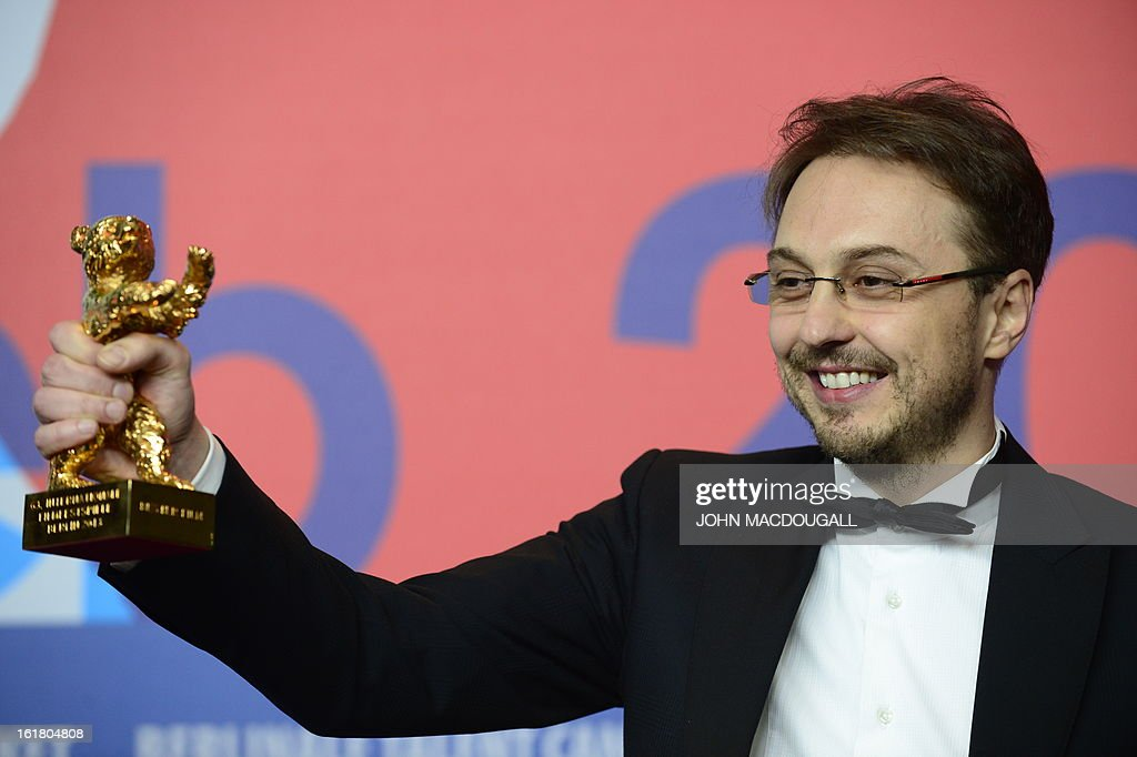 Romanian director Calin Peter Netzer presents the Golden Bear for the Best Film he received for the movie Pozitia Copilului during a press conference...