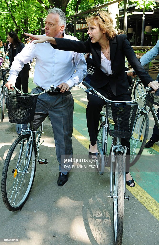 Romanian Environment Minister Laszlo Borbely (L) and European Commissioner for Climate Action Connie Hedegaard (R) ride bicycles in Bucharest's Herastrau Park on June 3, 2010. As part of an outdoor event to create awareness in ecological friendly means, EU Commissioner Connie Hedegaard and Minister Borbely highlights the importance of using bicycles as an alternative to urban transport by car.
