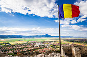 Romanian flag flying above the town of Rasnov, Transylvania, Romania. The flag flies against a bright blue sky and cloudscape, with the rural town of Rasnov spread out below, with the mountains at the