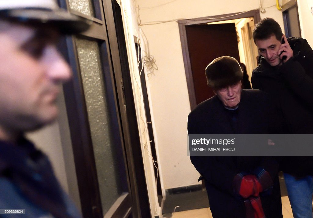 Romanian former communist prison chief Alexandru Visinescu (C) is escorted by police to jail from his apartment in Bucharest on February 10, 2016 as a Romanian appeal court upheld a 20-year jail term for the former head of a notorious Communist-era prison, convicted of crimes against humanity. The High Court in Bucharest rejected the appeal by Visinescu, 90, who was found guilty in July 2015, 26 years after the collapse of the totalitarian regime of Nicolae Ceausescu. / AFP / DANIEL MIHAILESCU