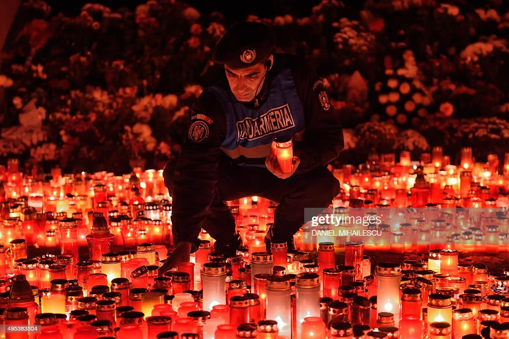 A Romanian gendarme places candles given by the people who came to pay respect for the victims of the fire at the 'Colectiv' nightclub in Bucharest...