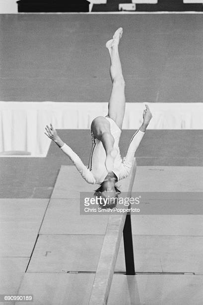 Romanian gymnast Nadia Comaneci pictured in action performing a somersault during competition on the balance beam part of the women's artistic team...