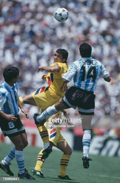 Romanian midfielder and captain of the national side Gheorghe Hagi pictured in action jumping for the ball along with Argentine players Diego Simeone...