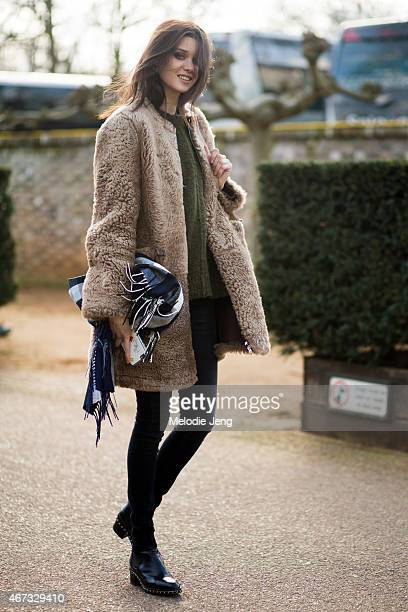 Romanian model Diana Moldovan exits the Burberry Prorsum show in a Carolina Herrera bag Chanel boots a Burberry scarf Marni and Isabel Marant during...