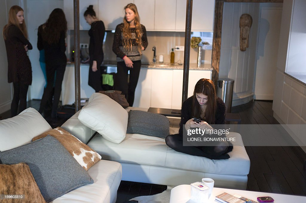 LACUT - Romanian model Ioana Timoce (R) looks at her mobile phone next to roomates in the appartment rented by their agency for the fashion week on January 16, 2013 in Paris. Ioana Timoce works with the agency H Model Management for the fashion week in Paris.