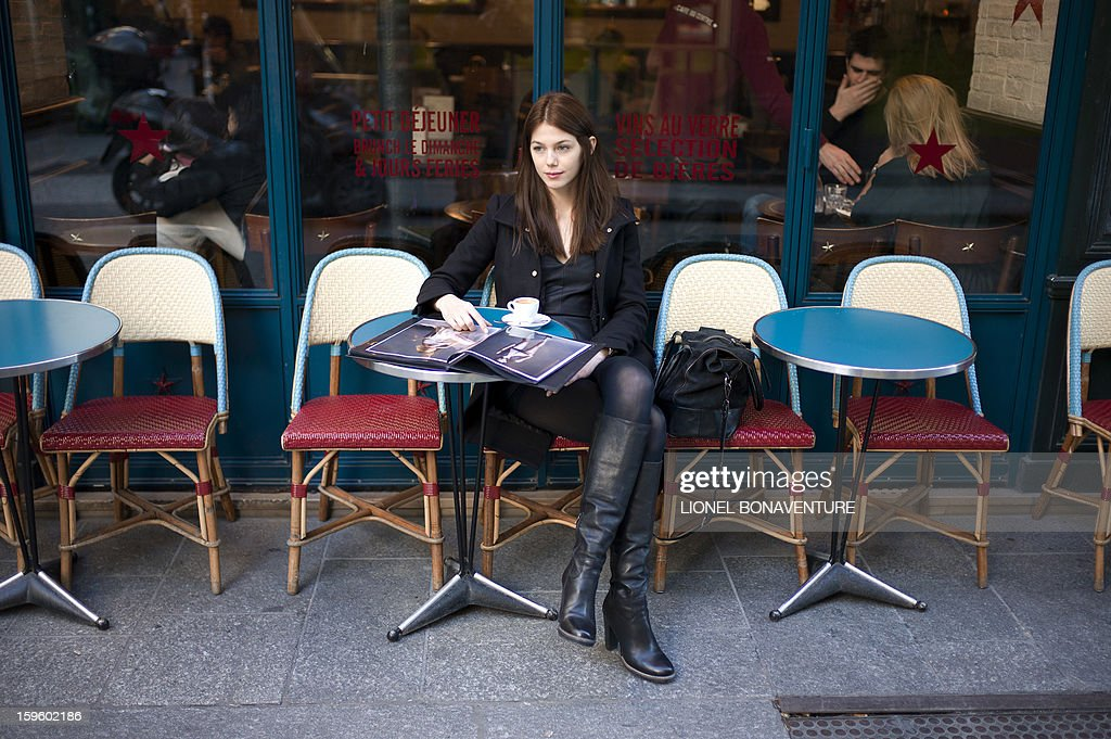 LACUT - Romanian model Ioana Timoce sits at a cafe terrace with her personal book on January 16, 2013 in Paris. Ioana Timoce works with the agency H Model Management for the fashion week in Paris.